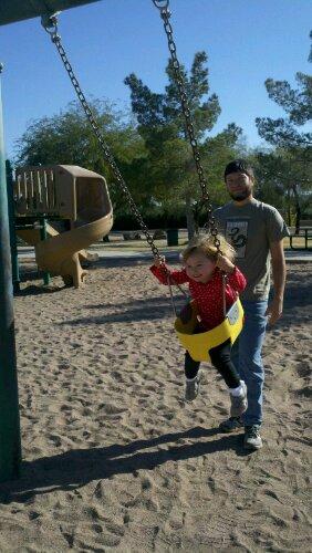 Jay pushing Laya on the swings